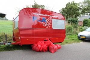 10 kg afval tegen onze rode caravan.